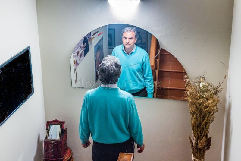 Hombre de mediana edad en casa delante del espejo fotos de archivo libres de regalías