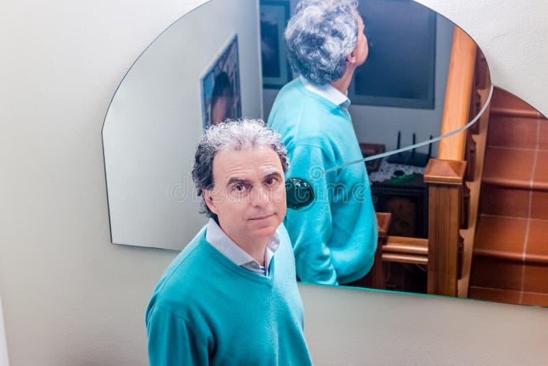 Hombre de mediana edad en casa delante del espejo imagen de archivo libre de regalías