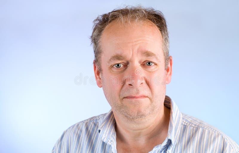 Hombre de mediana edad infeliz sobre algo fotos de archivo
