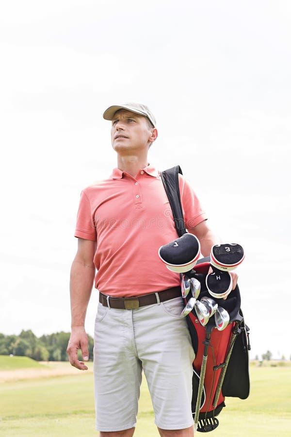 Hombre de mediana edad pensativo que parece ausente mientras que lleva la bolsa de golf contra el cielo claro imagenes de archivo