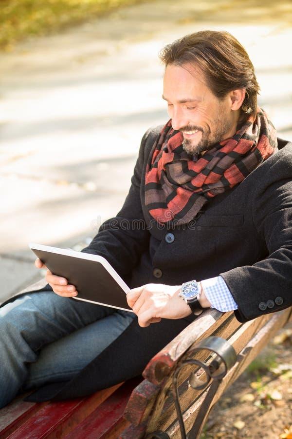 Hombre de mediana edad que descansa sobre el banco al aire libre fotografía de archivo