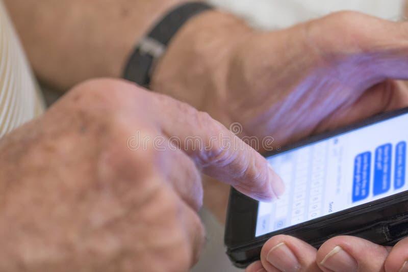 Hombre de mediana edad que mecanografía un mensaje de texto fotografía de archivo libre de regalías