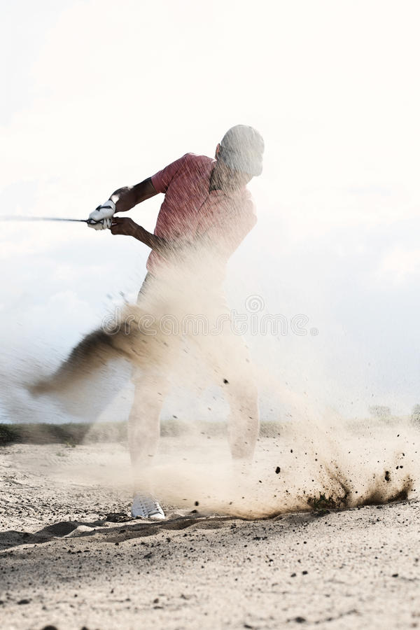 Hombre de mediana edad que salpica la arena mientras que juega en el campo de golf fotos de archivo