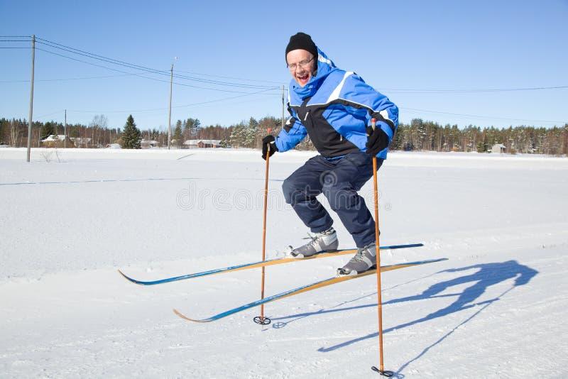 Hombre de mediana edad que salta en el aire con los esquís imagenes de archivo