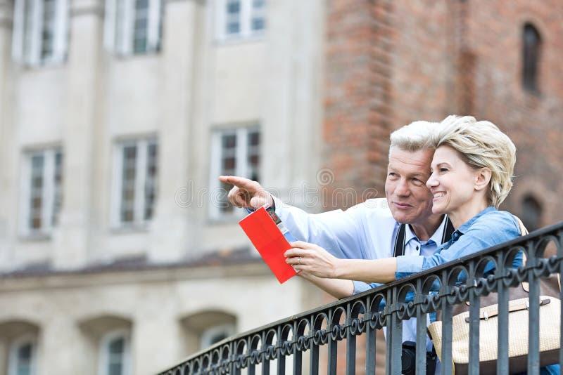 Hombre de mediana edad sonriente que muestra algo a la mujer con la guía turística en ciudad imagen de archivo