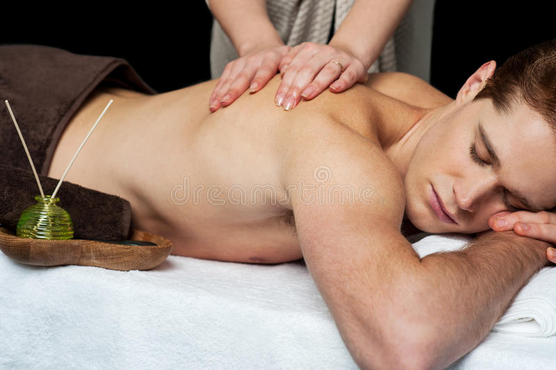Hombre de mentira que consigue un masaje trasero foto de archivo