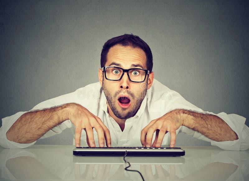 Hombre de mirada Nerdy en vidrios que mecanografía en el teclado imagen de archivo libre de regalías