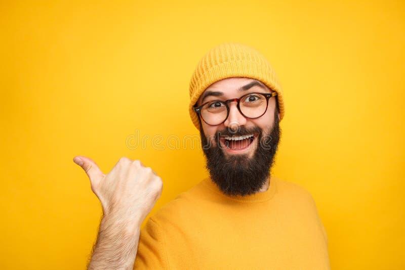 Hombre de moda colorido que señala lejos en amarillo imagen de archivo libre de regalías