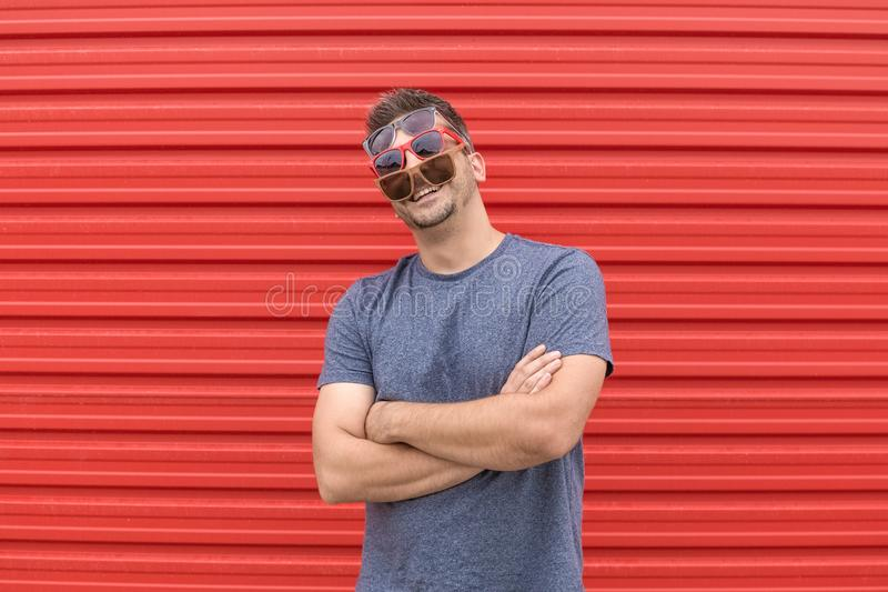 Hombre de moda con tres diferentes tipos de gafas de sol en fondo rojo foto de archivo libre de regalías