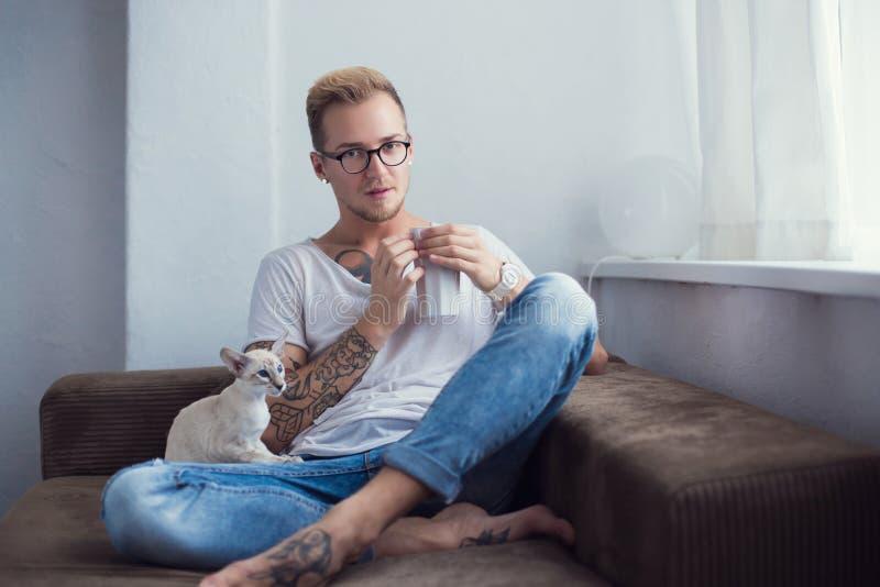 Hombre de moda joven y un gato en casa Shorthair oriental pets Retrato interior imágenes de archivo libres de regalías