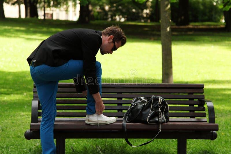 Hombre de moda que ata su zapato fotos de archivo