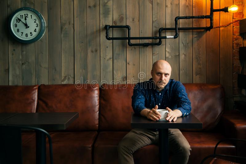 Hombre de moda serio joven que se sienta solamente en café desván-diseñado fotos de archivo