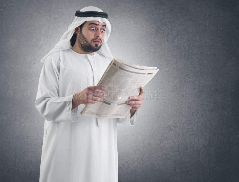 Hombre de negocios árabe dado una sacudida eléctrica leyendo el periódico fotografía de archivo
