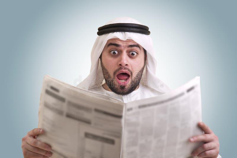Hombre de negocios árabe dado una sacudida eléctrica mientras que lee el newspape foto de archivo