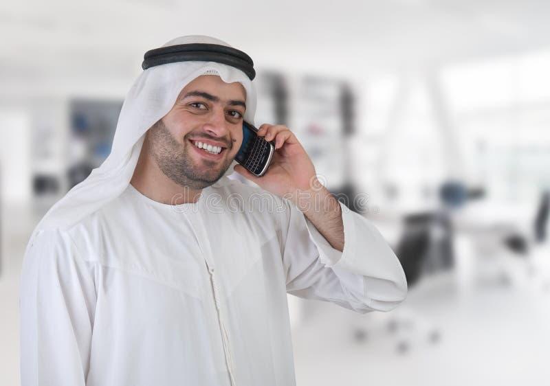 Hombre de negocios árabe en la oficina que tiene una llamada de teléfono fotografía de archivo libre de regalías