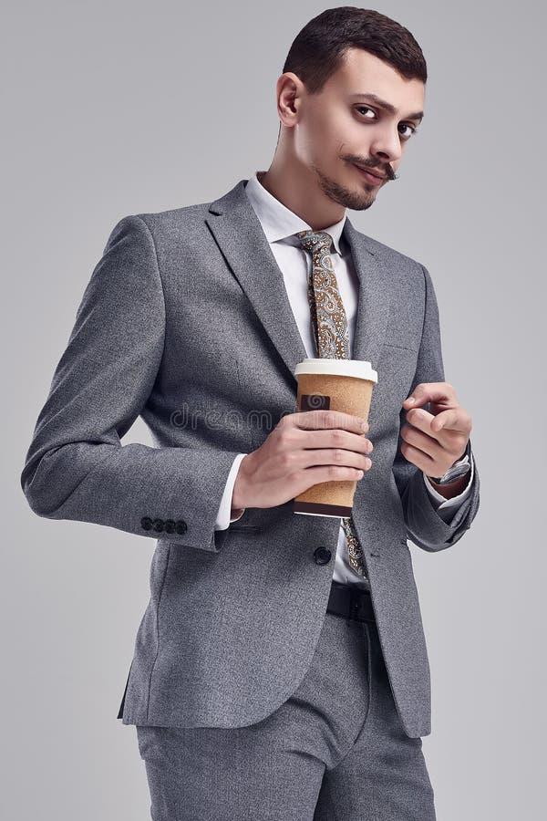 Hombre de negocios árabe joven hermoso con el bigote en traje gris de la moda fotografía de archivo