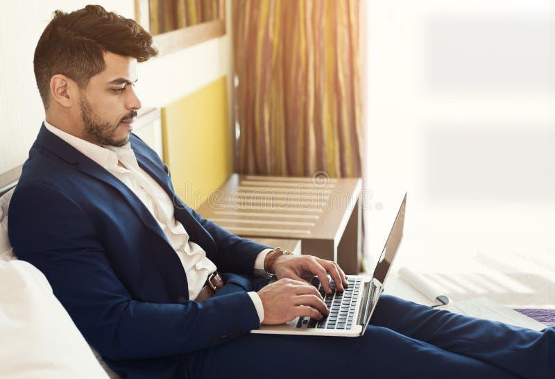 Hombre de negocios árabe que miente en cama en hotel y que usa el ordenador portátil fotos de archivo libres de regalías