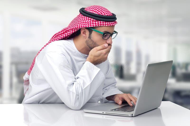 Hombre de negocios árabe que mira chocado su ordenador fotografía de archivo