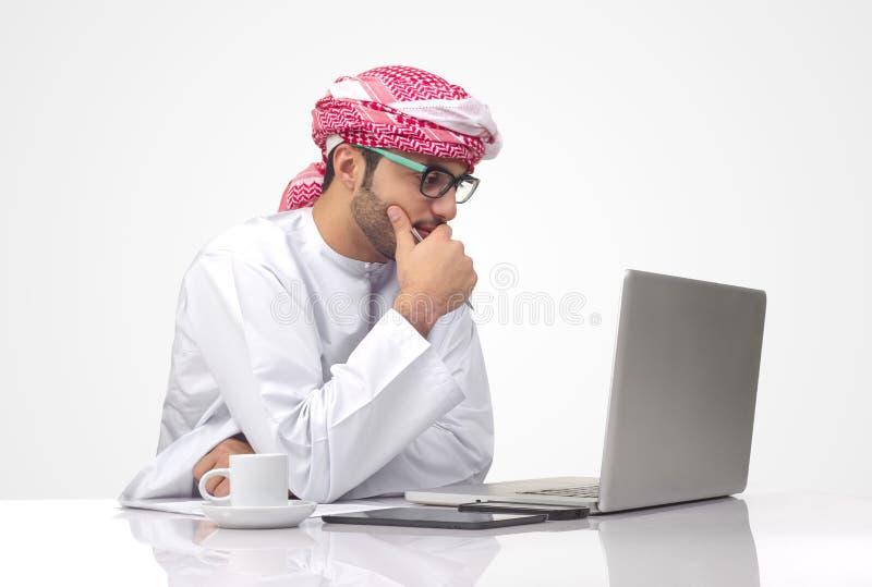 Hombre de negocios árabe que trabaja en su cuaderno fotos de archivo