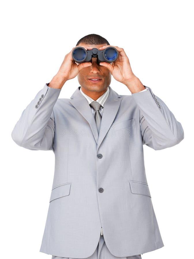 Hombre de negocios étnico atractivo usando los prismáticos imagen de archivo