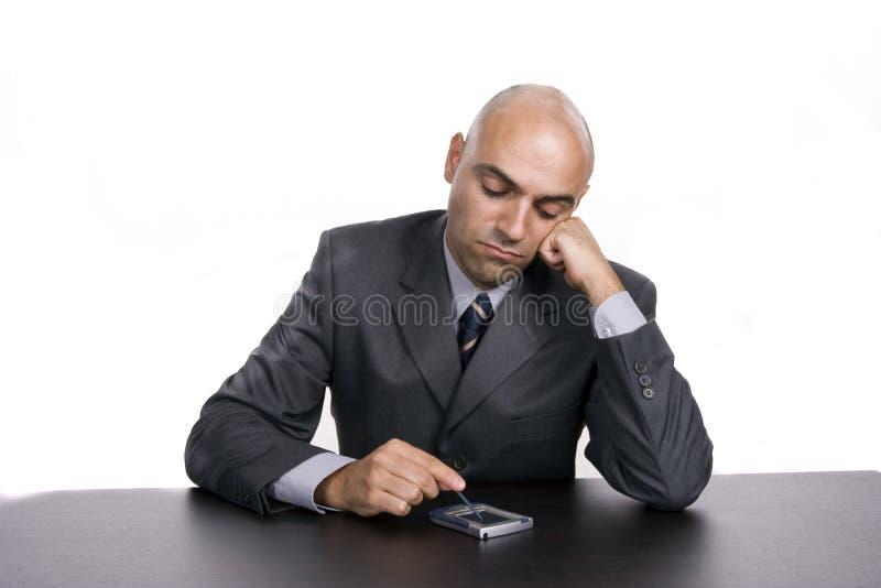 Hombre de negocios aburrido joven, trabajando en el escritorio imagen de archivo libre de regalías