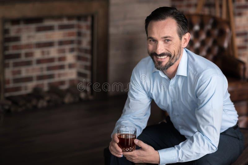 Hombre de negocios acertado alegre que disfruta de su bebida alcohólica fotografía de archivo libre de regalías