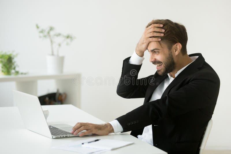 Hombre de negocios acertado chocado por el lookin en línea increíble del triunfo fotografía de archivo