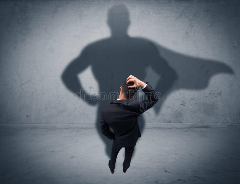 Hombre de negocios acertado con la sombra del super héroe imagen de archivo