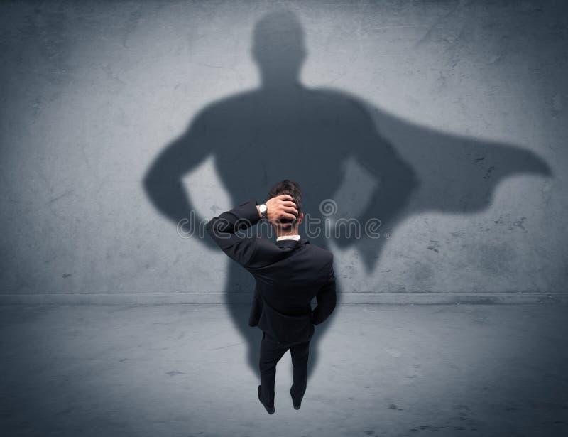 Hombre de negocios acertado con la sombra del super héroe foto de archivo