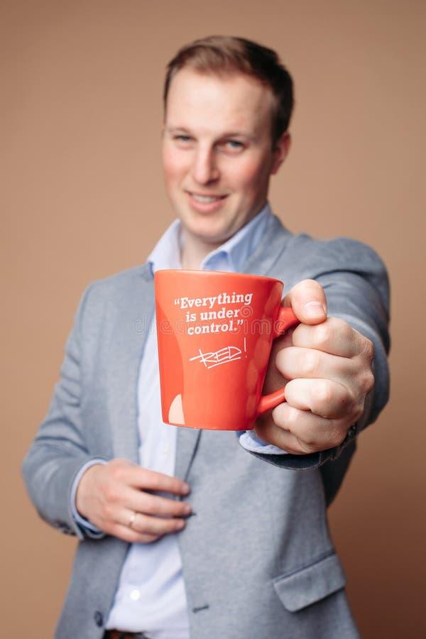 Hombre de negocios acertado con la taza con lema el tranquilizar foto de archivo libre de regalías