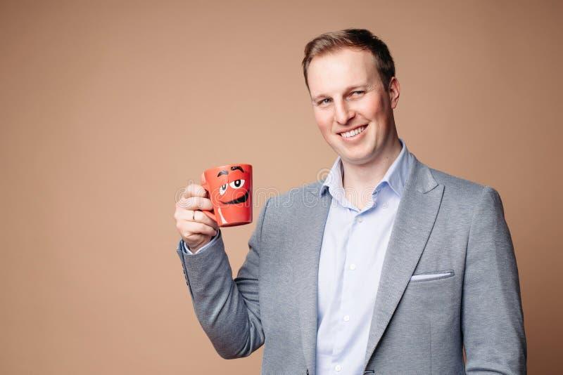 Hombre de negocios acertado con la taza con lema el tranquilizar fotografía de archivo