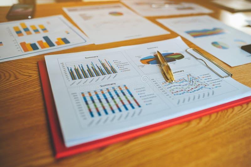 Hombre de negocios acertado In del escritorio de trabajo y del documento de trabajo su trabajo y en el otro trabajo El equipo de  fotografía de archivo