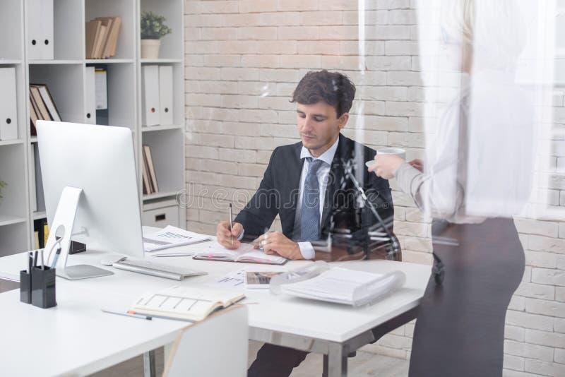 Hombre de negocios acertado en oficina con la secretaria imagen de archivo libre de regalías
