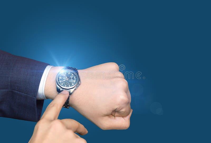 Hombre de negocios acertado en traje formal que comprueba tiempo fotografía de archivo libre de regalías