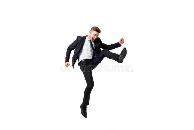 Hombre de negocios acertado joven en el júbilo del traje, saltando sobre el fondo blanco imagen de archivo