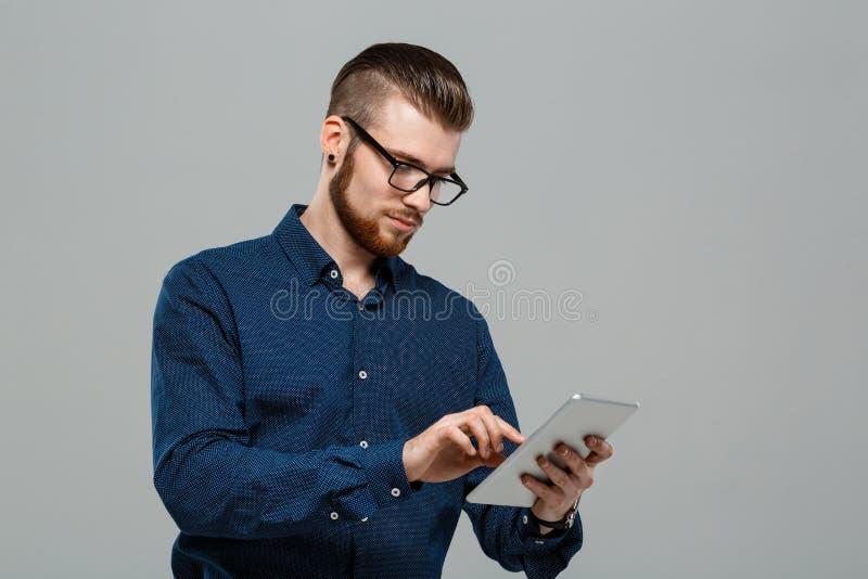 Hombre de negocios acertado joven que mira la tableta sobre fondo gris imagen de archivo libre de regalías