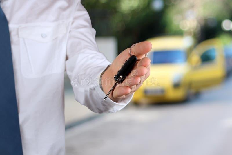 Hombre de negocios acertado joven que ofrece una llave del coche Primer de la mano del conductor que muestra llave imagenes de archivo