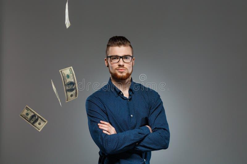 Hombre de negocios acertado joven que presenta entre el dinero que cae sobre fondo oscuro imagen de archivo