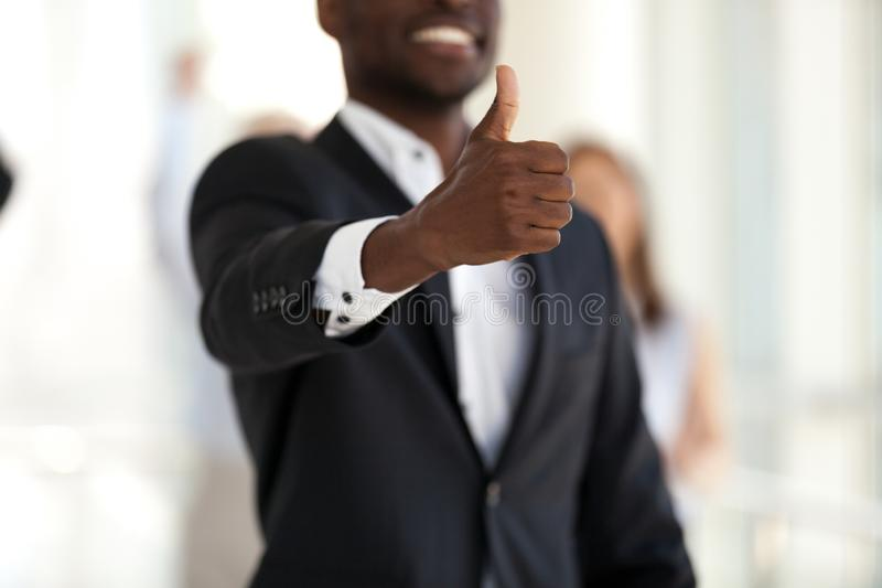 Hombre de negocios acertado negro que muestra los pulgares para arriba, foco a mano imagen de archivo