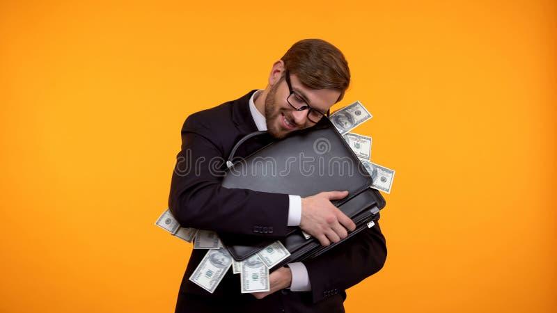 Hombre de negocios acertado que abraza la cartera por completo de los billetes de banco del d?lar, salud foto de archivo libre de regalías