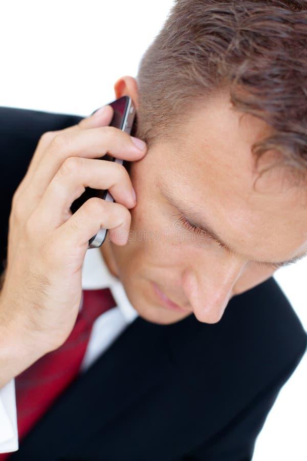 Hombre de negocios acertado que habla en el teléfono y el worki fotografía de archivo libre de regalías