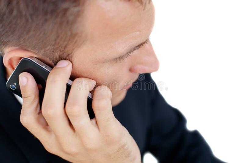 Hombre de negocios acertado que habla en el teléfono y el worki foto de archivo