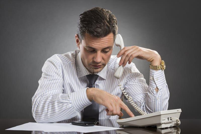 Hombre de negocios acertado que marca en el teléfono imagen de archivo