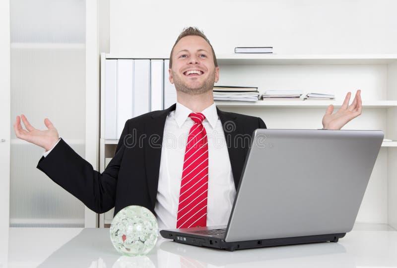 Hombre de negocios acertado que ríe con las manos para arriba y el ordenador portátil fotografía de archivo