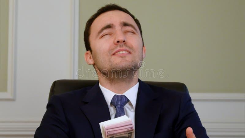 Hombre de negocios acertado que ruega para muchos en la oficina foto de archivo libre de regalías