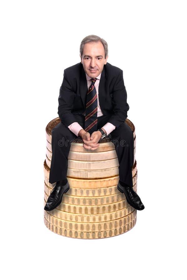 Hombre de negocios acertado que se sienta en una pila de monedas fotos de archivo libres de regalías
