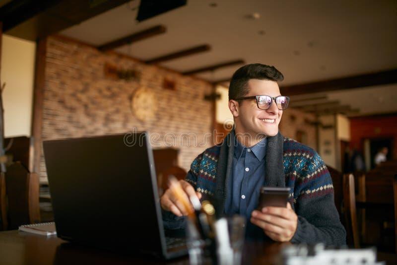 Hombre de negocios acertado que sostiene smartphone moderno móvil El inconformista feliz con un teléfono moderno disfruta de noti fotografía de archivo libre de regalías