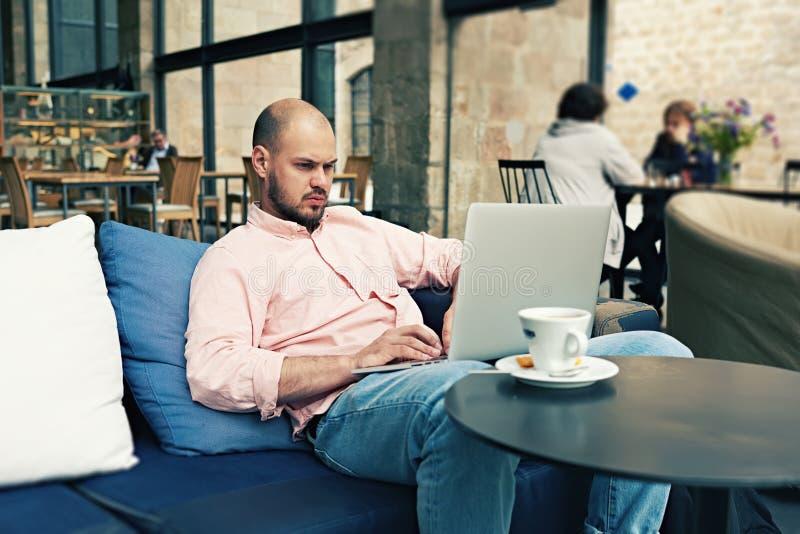 Hombre de negocios acertado que tiene descanso para tomar café mientras que está leído un ciertas noticias en el ordenador portát fotos de archivo