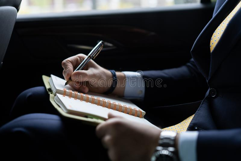 Hombre de negocios acertado sonriente que trabaja con los papeles en el asiento trasero de un coche y de mirar hacia fuera la ven foto de archivo