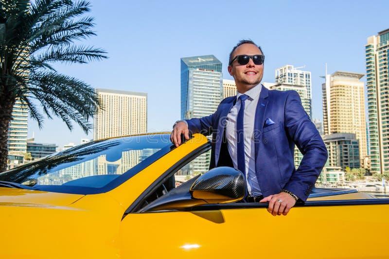 Hombre de negocios acertado de yang en coche amarillo del cabrio imagen de archivo